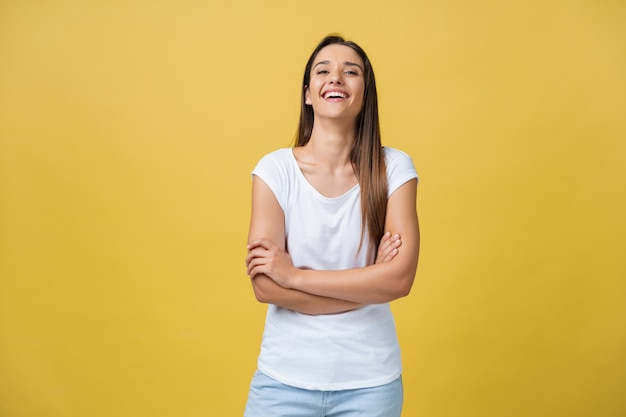 Portrait young beautiful caucasian girl with an white shirt laughing over yellow background.
