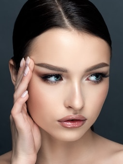 Portrait of young beautiful caucasian woman touching her face. cleaning skin, skincare, cosmetology concept