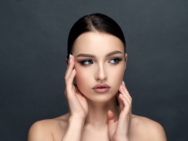 Portrait of young beautiful caucasian woman touching her face isolated. cleaning skin, skincare, cosmetology concept