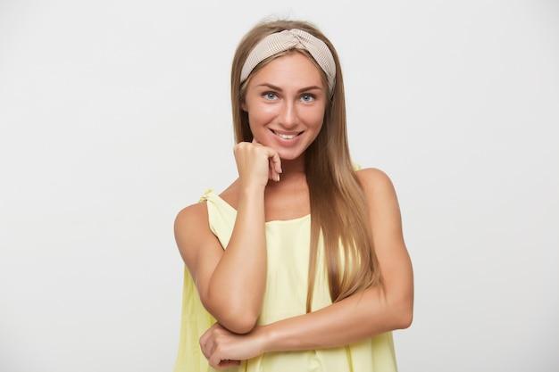 Ritratto di giovane bella signora bionda dai capelli lunghi allegra che indossa la fascia beige mentre posa su sfondo bianco, sorridendo piacevolmente alla telecamera e tenendo la mano alzata sul viso
