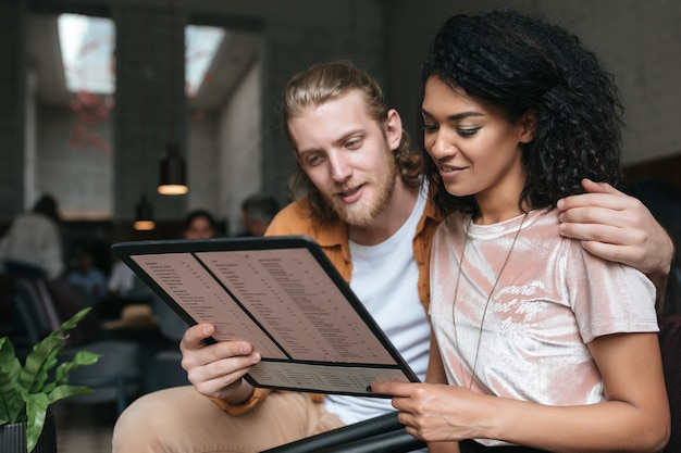 Portrait of young beautiful couple sitting in restaurant with menu in hands