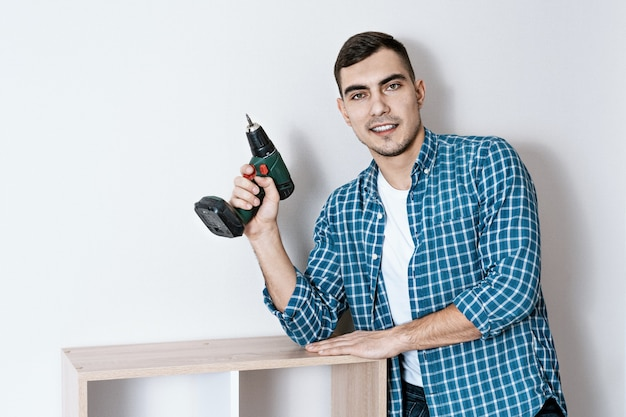 Portrait of a young beautiful european man with an electric screwdriver in his hand, a collector of furniture
