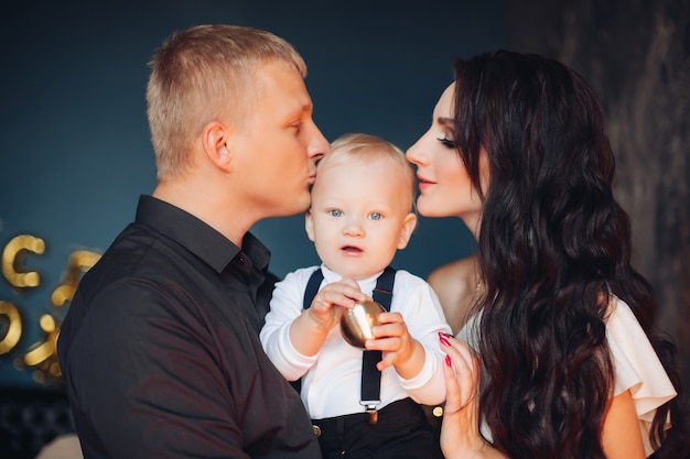 Portrait of young beautiful family of three poses for the family photo