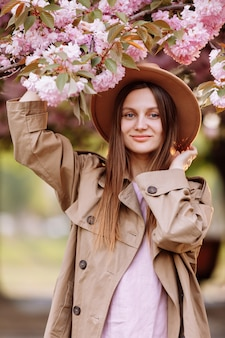 Portrait of young beautiful fashionable girl in hat posing near blooming tree with pink flowers on a sunny day. pink flowers blooming in uzhhorod, ukraine. blossom around. spring time concept