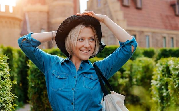 中世の旧市街で黒い帽子をかぶった若い美しいファッショナブルな幸せな女性のポートレート。