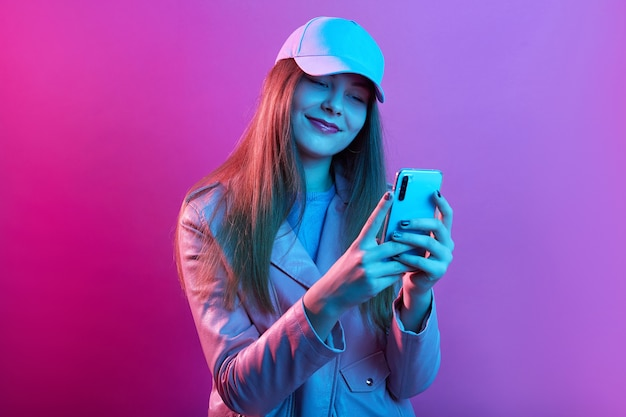 Portrait of young beautiful fashionable model wearing leather baker and baseball cap, holding smart phone in hands