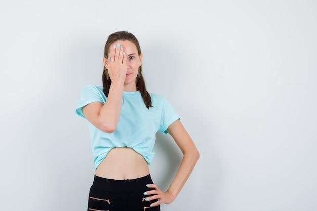 Ritratto di giovane bella donna che copre l'occhio con la mano in maglietta, pantaloni e guardando curiosa vista frontale
