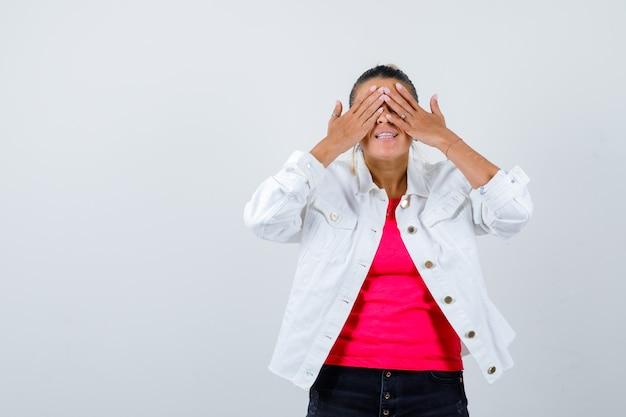 Ritratto di giovane bella donna che copre gli occhi con le mani in maglietta, giacca bianca e guarda curiosa vista frontale