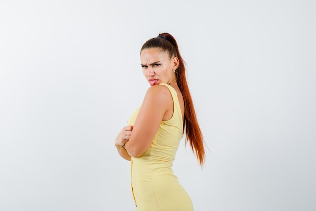 Portrait of young beautiful female holding arms folded while sticking tongue out in dress and looking furious