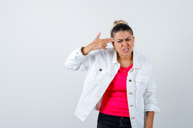 Portrait of young beautiful female making suicide gesture in t-shirt, white jacket and looking annoyed front view