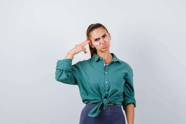 Portrait of young beautiful female making suicide gesture while curving lower lip in green shirt and looking upset front view