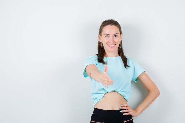 Portrait of young beautiful female offering handshake for greeting in t-shirt, pants and looking merry front view