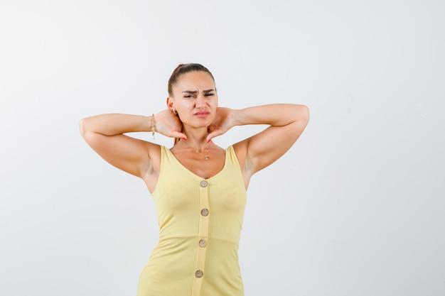 Ritratto di giovane bella donna che soffre di dolore al collo in abito e guardando malessere vista frontale