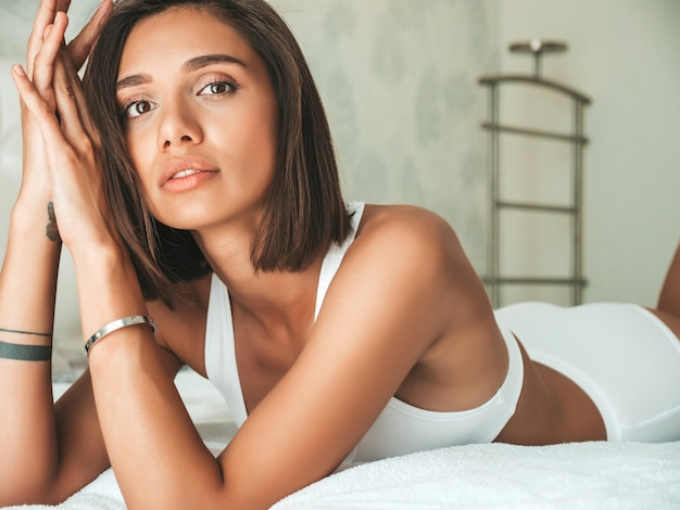 Portrait of young beautiful  female in white lingerie and towel on head