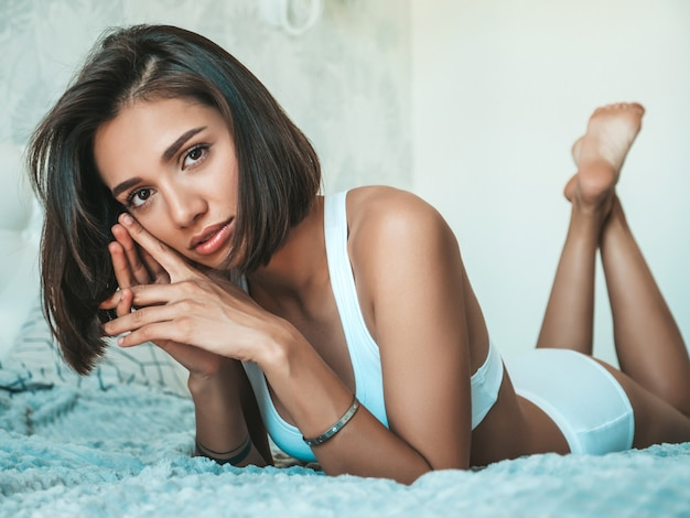 Portrait of young beautiful female in white lingerie