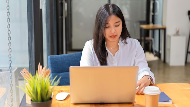 Portrait of young beautiful female in white shirt working with laptop in comfortable office room