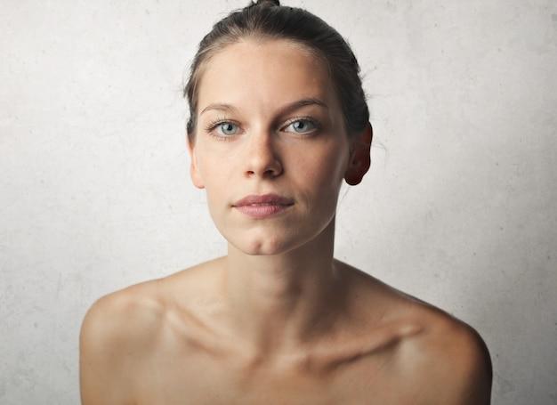 Ritratto di una giovane donna bellissima con pelle perfetta e spalle nude