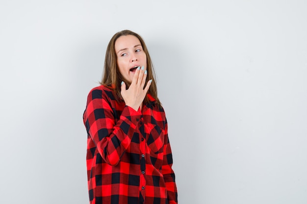 Portrait of young beautiful female yawning, looking away in casual shirt and looking sleepy front view