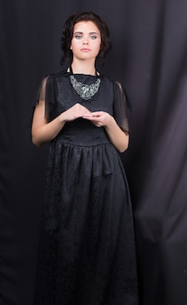 Portrait of a young beautiful girl in a black dress standing on a dark background.