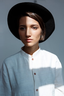 Portrait of young beautiful girl in black hat.
