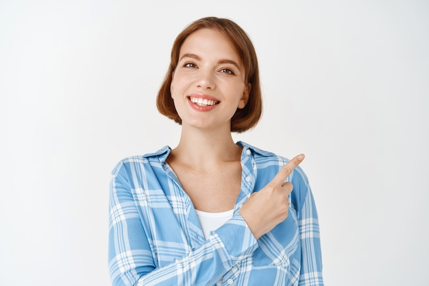 Portrait of young beautiful girl in checked shirt, pointing at upper right corner, smiling.  woman with short hair and white smile make announcement
