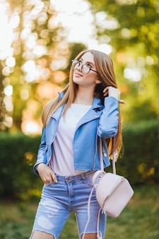 Ritratto di una giovane bella ragazza con gli occhiali in jeans con pantaloni alla moda