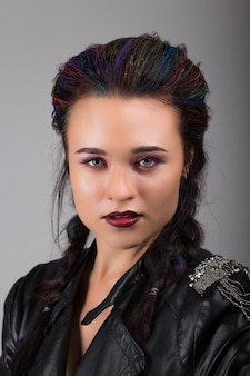 Portrait of a young beautiful girl in a leather jacket with gray eyes and makeup.