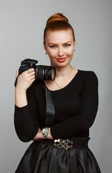 Portrait of a young beautiful girl photographer with his camera. studio photography. photosession