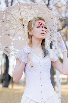 Portrait of young beautiful girl with blood halloween make-up on her face and white dress