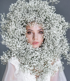 Portrait of a young beautiful girl with circle made of fresh gypsophila on the face dressed in white blouse