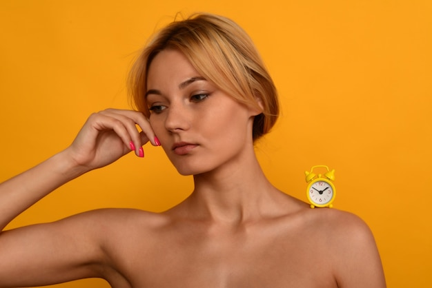 Portrait of a young beautiful girl with the clock on the shoulder. the concept of aging. time and youth are not eternal