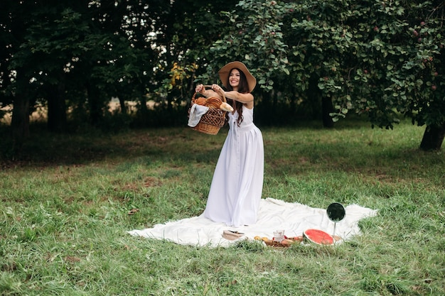 Il ritratto di una giovane bella ragazza con i denti anche bianchi, un bel sorriso con un cappello di paglia e un lungo vestito bianco fa un picnic in giardino.