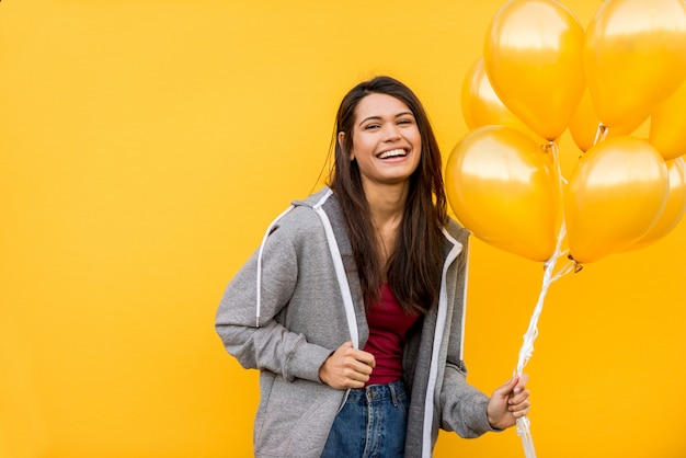 Portrait of young beautiful girl with orange balloons