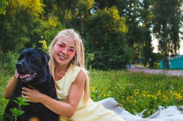 Portrait of a young beautiful girl with white hair with a black dog in the park