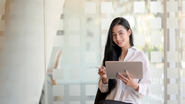 Portrait of young beautiful graphic designer working on her project with tablet and looking at the camera while standing in modern office