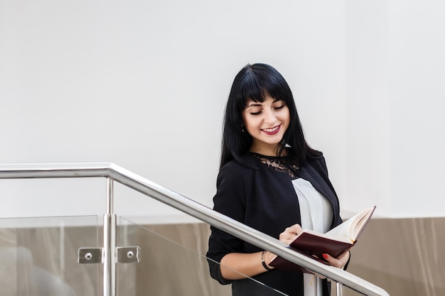 Portrait of young beautiful happy brunette woman dressed in a black business suit working with a notebook, standing in office, smiling.