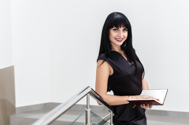 Portrait of young beautiful happy brunette woman dressed in a black business suit working with a notebook, standing in a office, smiling.
