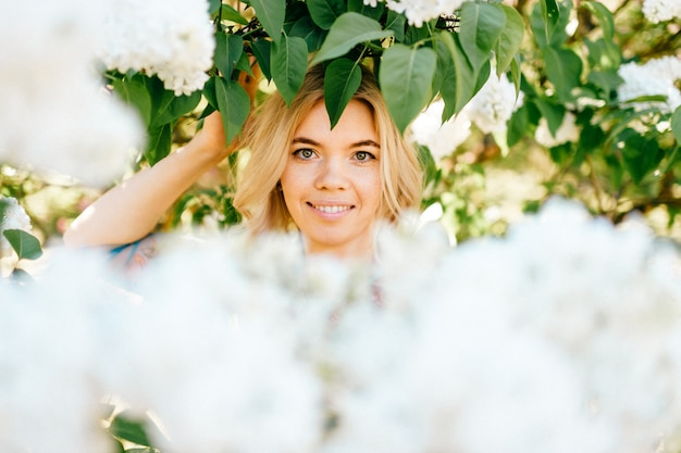 Portrait of young beautiful happy cheerful smiling positive blonde girl looking through branches with white flowers in summer blooming park.
