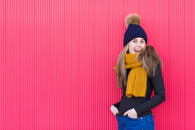 Portrait a young beautiful happy woman over red wall wearing scarf and hat