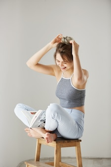 Portrait of young beautiful happy woman smiling laughing correcting hair bun sitting on chair over white wall at home.