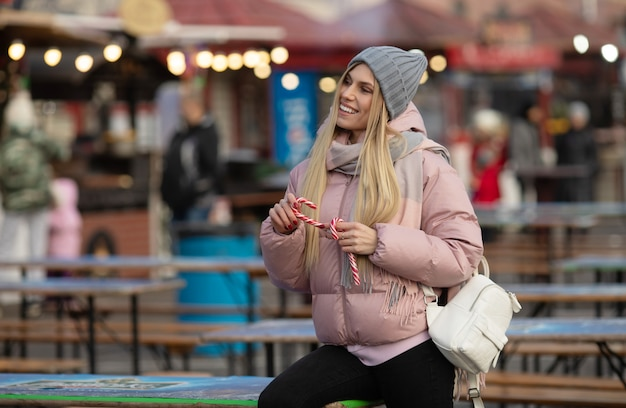 Portrait of a young beautiful happy woman with candy posing on the street of a european city. xmas.