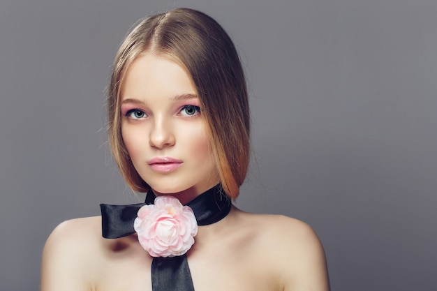 Portrait of young beautiful healthy woman with fancy pink rose ornament accessory