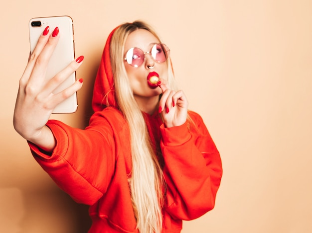 Portrait of young beautiful hipster bad girl in trendy jeans  clothes and earring in her nose.sexy carefree smiling blond woman takes selfie.positive model licking round sugar candy
