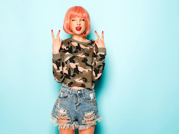 Portrait of young beautiful hipster bad girl in trendy jeans shorts and earring in her nose.sexy carefree smiling woman posing in studio in pink wig.positive model having fun.shows peace sign