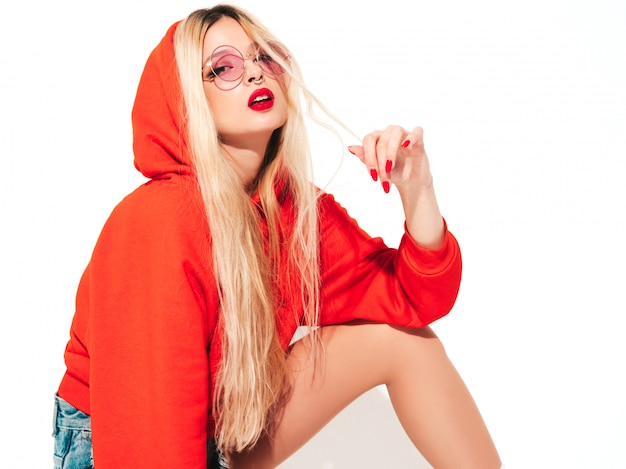 Portrait of young beautiful hipster bad girl in trendy red  hoodie and earring in her nose.sexy carefree smiling blond woman sitting in studio.positive model having fun.isolated on white