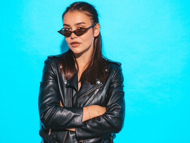 Portrait of young beautiful hipster  bad girl in trendy summer black leather jacket and sunglasses. sexy carefree woman isolated on blue. brunette model posing