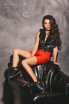 Portrait of young beautiful hipster girl in trendy summer red skirt and jacket. sexy carefree brunette woman model with makeup and hairstyle sitting in black leather chair in studio