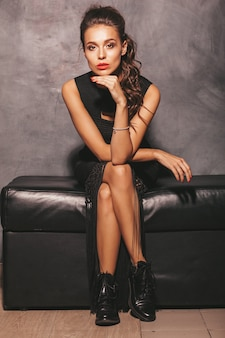 Portrait of young beautiful hipster woman in trendy summer black dress. sexy carefree woman posing near wall. brunette model with makeup and hairstyle. sitting on chair