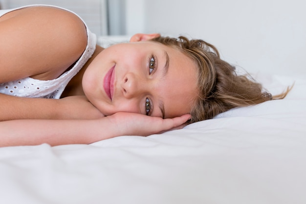 Portrait of a young beautiful kid resting on bed and smiling. white room.