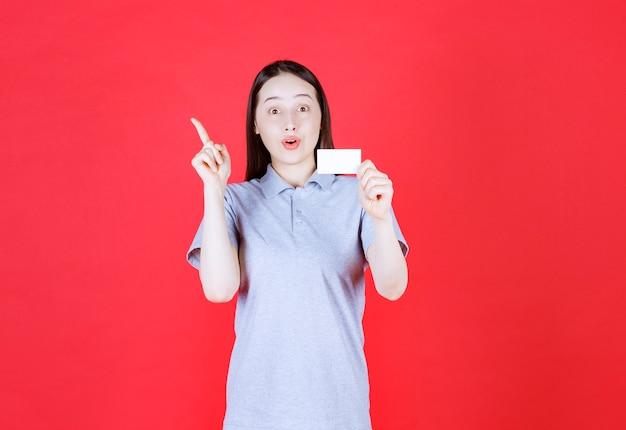 Ritratto di giovane bella signora che tiene il suo biglietto da visita e punta il dito in su